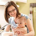 mother and baby using faucet
